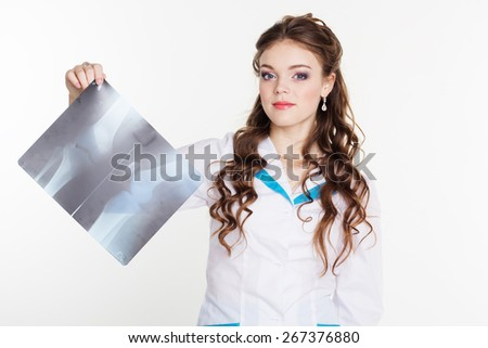 Young female intern looking at the x-ray picture of knee in hospital - stock photo