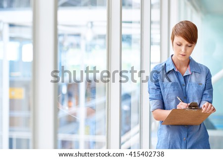 Young female intern taking notes on clipboard next to windows - stock photo