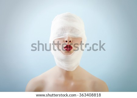 Young female is sending a kiss after her plastic surgery with really dark lipstick on her lips. Against blue background and vignette. - stock photo