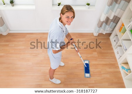 Young Female Janitor Mopping Wooden Floor In House