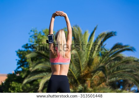Young female jogger with running armband on the arm working out outdoors in sunny summer day, fit woman dressed in sportswear with perfect slender figure doing stretching exercise in beautiful park - stock photo