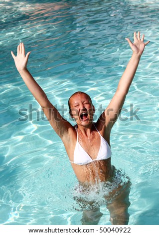 Young female jumping out of water in swimming pool,enjoying good time - stock photo