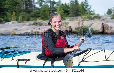 Young female kayaker in a kayak on a lake