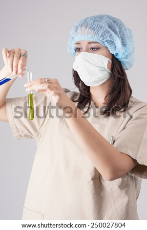Young Female Lab Staff Looking at Test Tube with Liquid. Over Gray Background. Vertical Image - stock photo