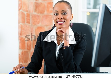 Young female lawyer or paralegal working in her office on a Computer or Pc - stock photo