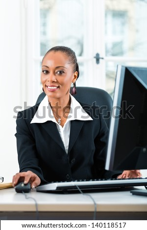 Young female lawyer or secretary working in her office on a Computer or Pc