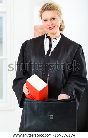 Young female lawyer working in her Office, she grabs a law book in her Briefcase - stock photo