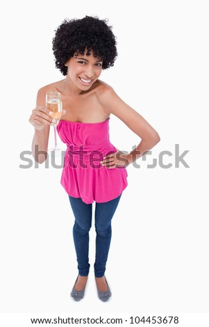 Young female leaning forward while drinking a glass of white wine - stock photo