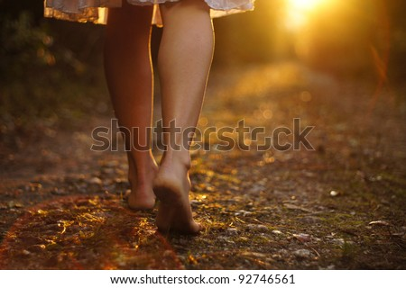 Young female legs walking towards the sunset on a dirt road - stock photo