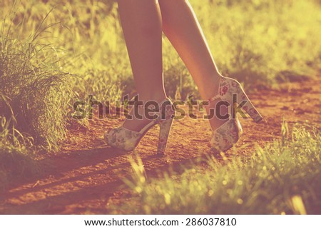 Young female legs walking towards the sunset on a dirt road. Instagram. shoes and woman legs. - stock photo