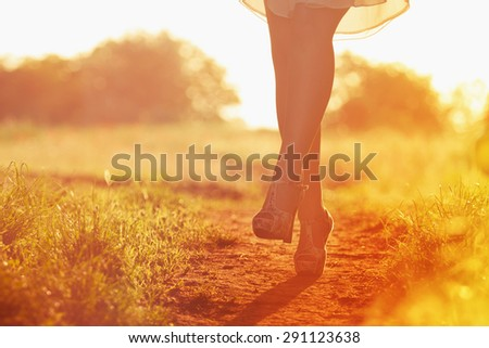 Young female legs walking towards the sunset on a dirt road. Instagram. shoes and woman legs.