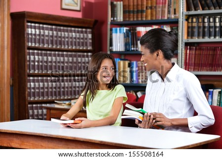 Young female librarian looking at schoolgirl while sitting with books at table in library - stock photo