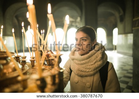 Young female lighting candles in a church during praying.Yellow votive candles burning.Woman praying to god at St. Alexander Nevsky Cathedral.Christianity.Strong christian religion faith - stock photo