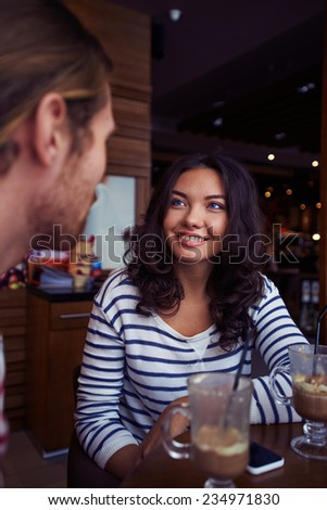 Young female looking at her boyfriend in cafe