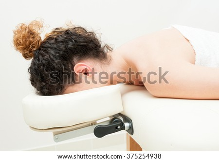 Young female lying and resting her head on massage table in the spa salon - stock photo