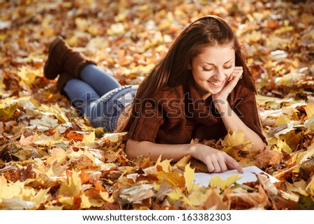 young female lying down on autumn leaves reading book