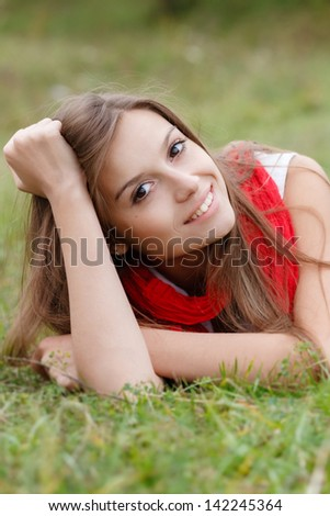 young female lying down on grass happy smiling