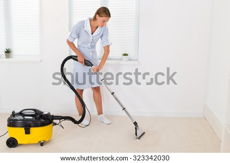 Young Female Maid Cleaning Floor With Vacuum Cleaner - stock photo