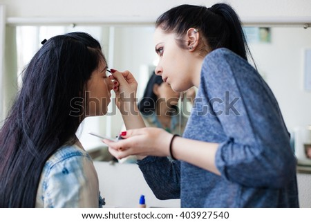 Young female  make-up artist working in her studio,  applying makeup on a client, preparing model to the beauty photo session - stock photo