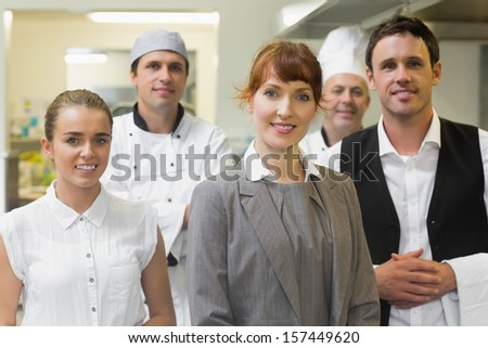 Young female manager posing in a modern kitchen with the staff - stock photo