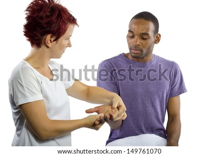young female masseuse applying pressure on male client's hand - stock photo