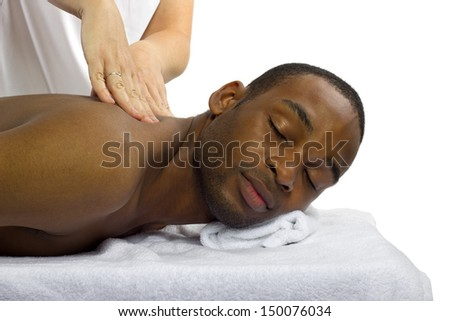 young female masseuse treating young male client with massage - stock photo