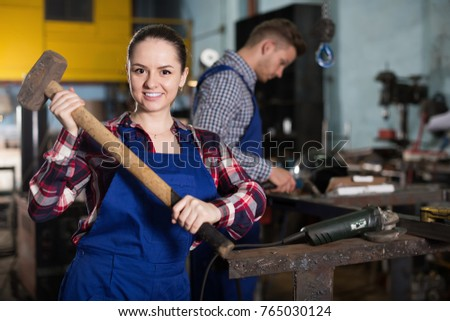 Young female  master is standing with sledgehammer in workshop