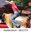 young female mechanical bull rider - stock photo