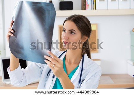 Young female medical doctor or intern looking at lungs x ray image standing at her office. Radiology, healthcare, medical service or education concept. - stock photo