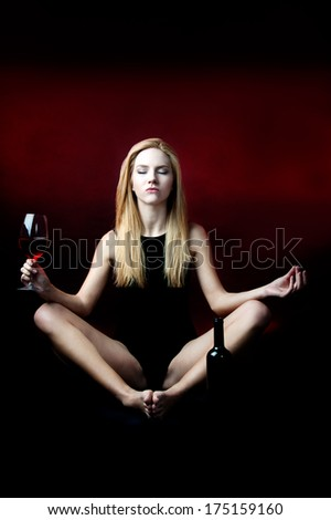 young female meditating with red wine against red background  - stock photo