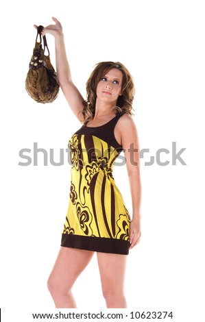 Young female model in a bold floral print mini dress holding her purse over her head - stock photo
