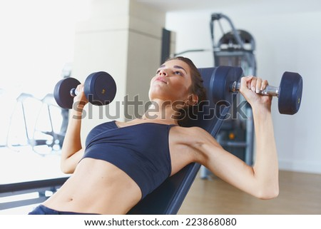 Young female model in fitness gym doing exercisec - stock photo
