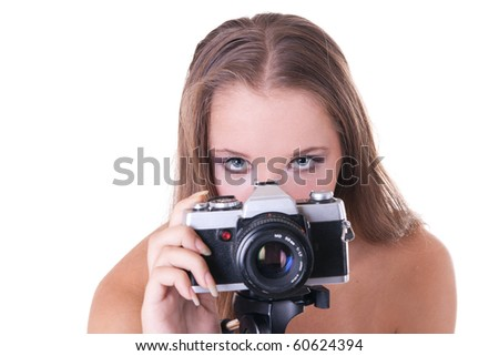 Young female model in polka dot dress posing with 35mm camera, isolated on white - stock photo