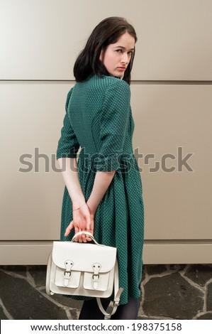 Young female model looking over her shoulder and wearing a green dress and a white purse - stock photo