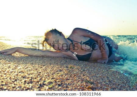 Young female model lying in water on golden sunset