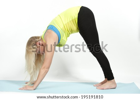 Young female model showing the downward facing dog pose in yoga - also known as Adho Mukha Svanasana. - stock photo