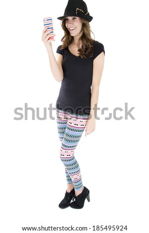 Young female model wearing colorful leggings, black heels, sun hat, and top.  Taking a selfie on her cell phone. - stock photo