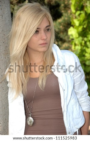Young female model wears casual clothes. Sits with natural face expression, teenage girl cool and relaxed.