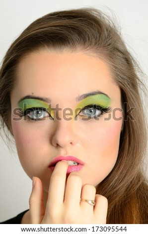 Young female model with colorful makeup. Face closeup portrait photo of teenager.