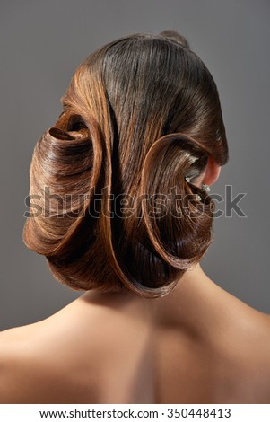 Young female model with elegant evening hairstyle posing back to the camera