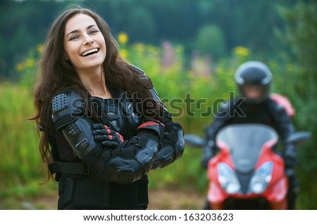 Young female motorcyclist on background of beautiful bike.