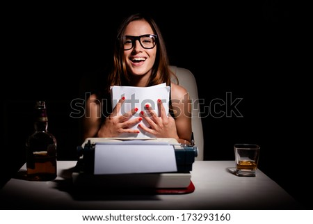 Young female novelist is happy because she finished writing her book - stock photo