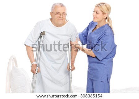 Young female nurse helping a senior patient with crutches isolated on white background - stock photo