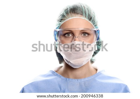 Young female nurse or doctor in surgical scrubs wearing a theatre gown, mask, goggles and a cap looking directly at the camera, head and shoulders isolated on white - stock photo