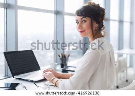 Young female office employee using laptop at work, smiling, looking camera. Businesswoman typing, blogging during working day. - stock photo
