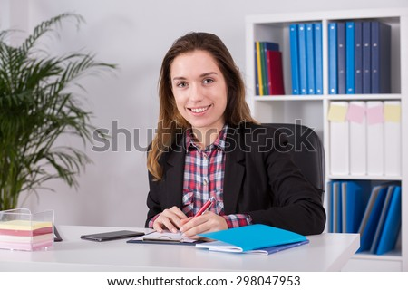 Young female office worker sitting at the desk