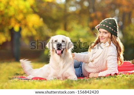 Young female on a grass with her labrador retriever dog in autumn posing outside  - stock photo