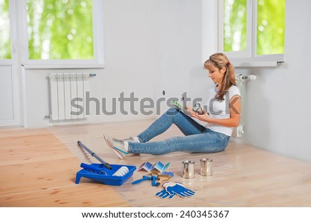 young female painter sitting on the floor holding color palette and looking on it