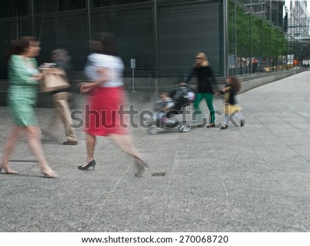 young female parent with stroller rushing on the street in intentional motion blur, business people walking by - stock photo