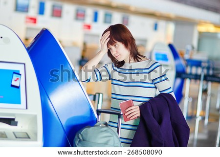 Young female passenger at the airport, doing self check-in, stressed and concerned. Missed, delayed or cancelled flight concept - stock photo